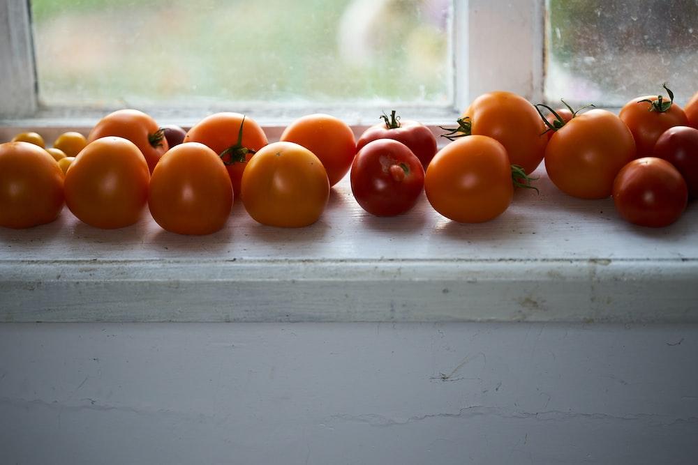 orange tomato on white wooden table