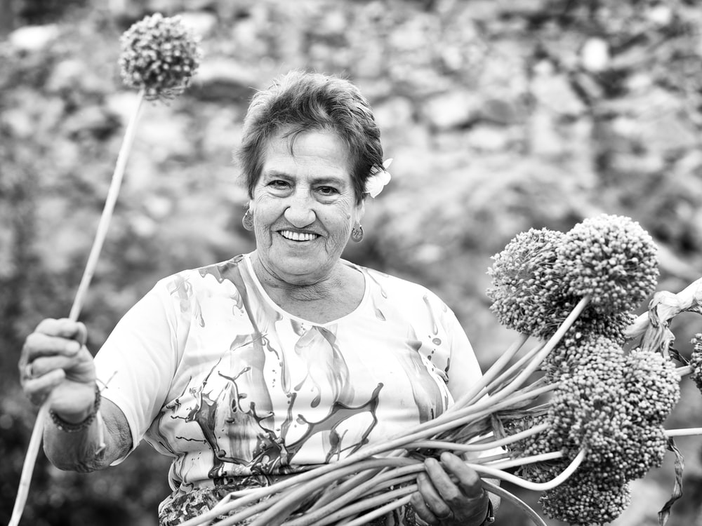 grayscale photo of woman holding bouquet of flowers