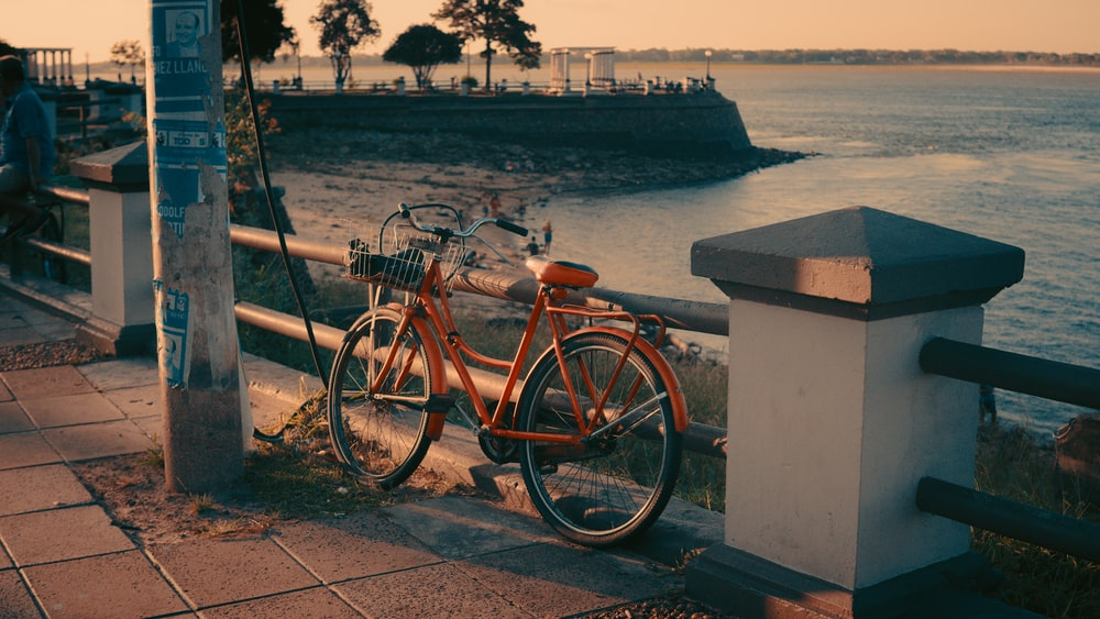 brown city bike parked beside white concrete post near body of water during daytime