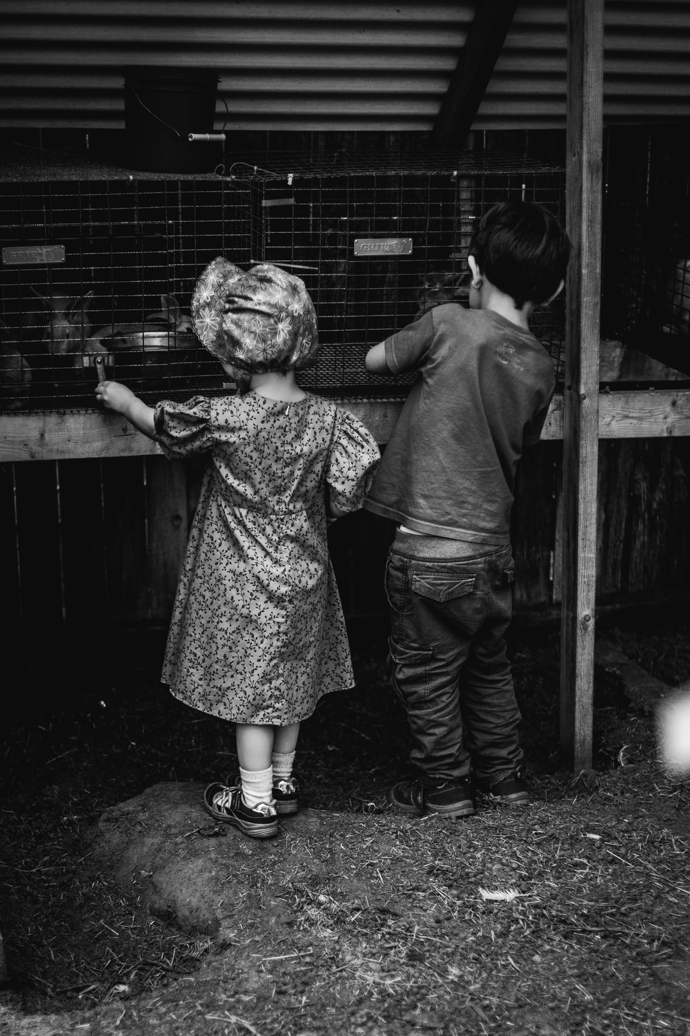 grayscale photo of 2 children standing beside fence