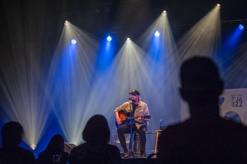 man in brown jacket singing on stage