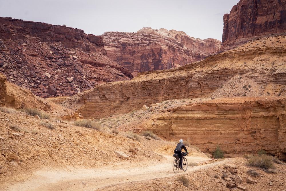 man in black jacket riding bicycle on brown dirt road during daytime