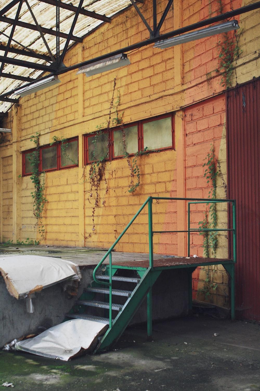 green metal railings near brown brick wall