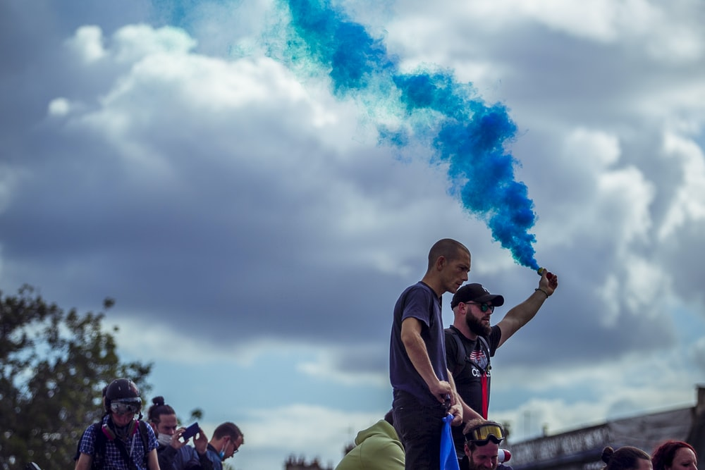 man in black t-shirt and green pants holding blue smoke