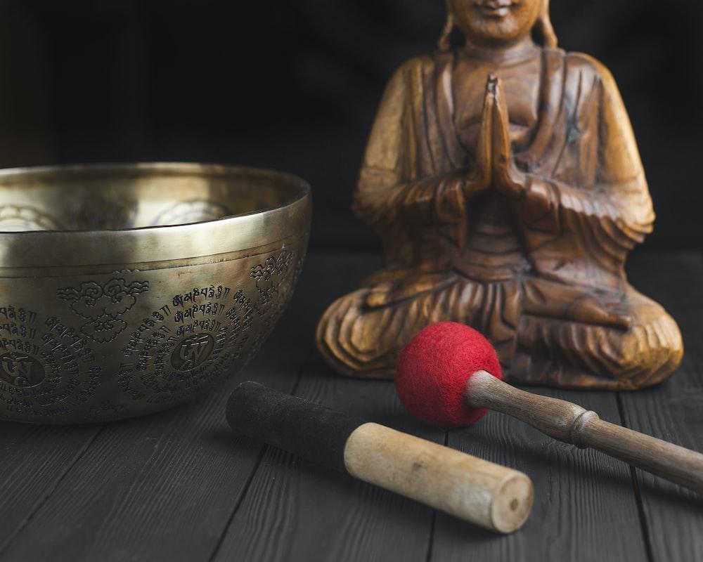 brass buddha figurine beside red and white stick