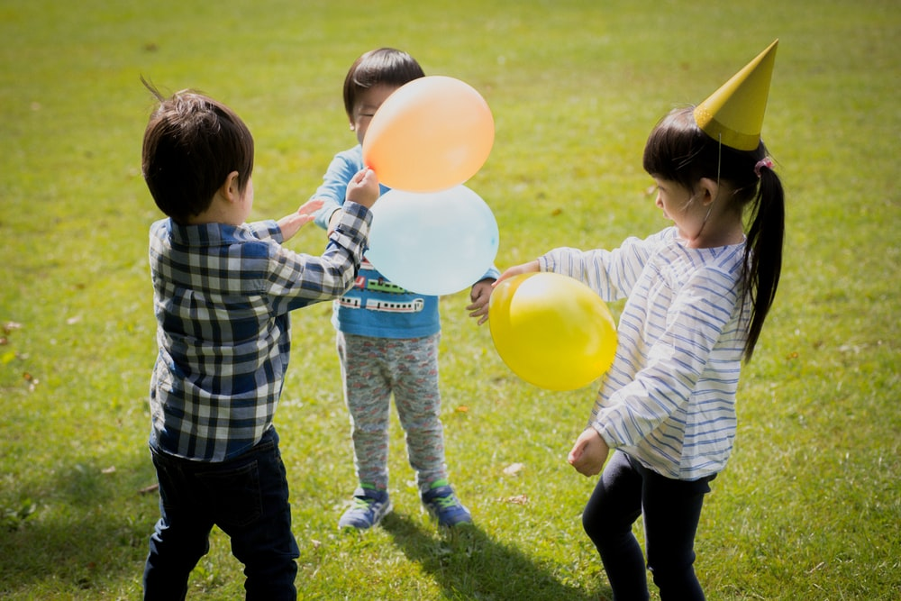 boy in blue and white plaid dress shirt holding yellow balloons