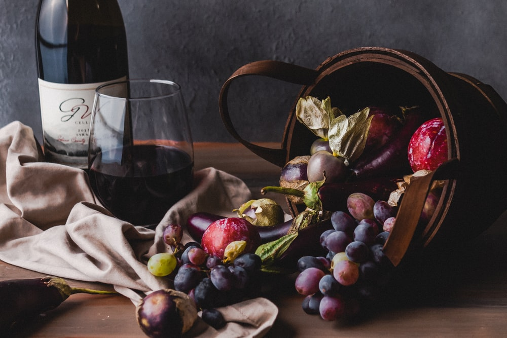 wine glass beside grapes and wine glass on table