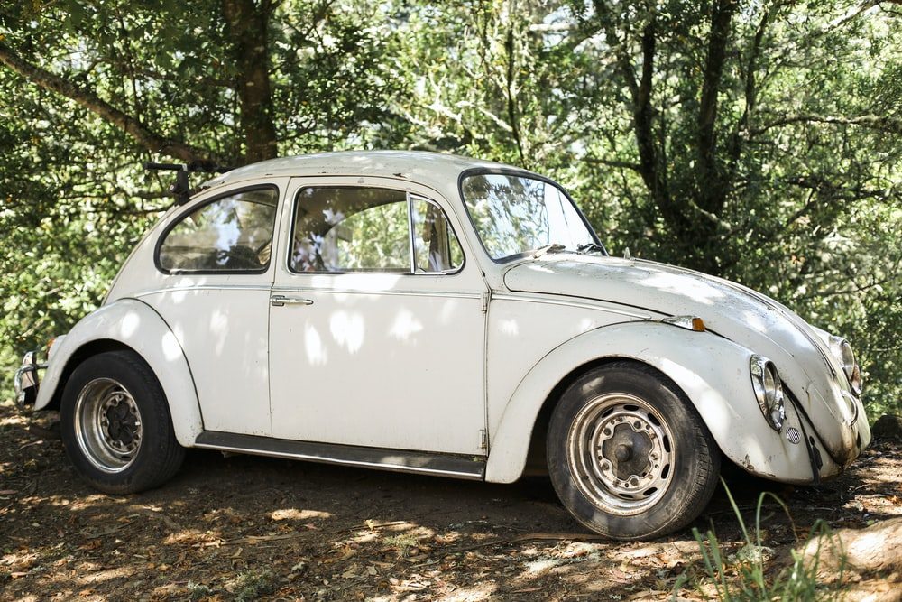 white volkswagen beetle parked on dirt road during daytime