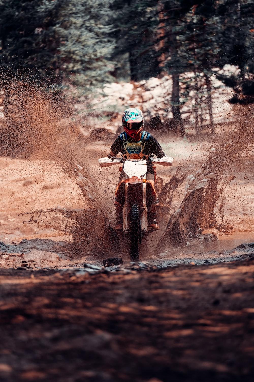 man in red helmet riding motocross dirt bike on dirt road during daytime