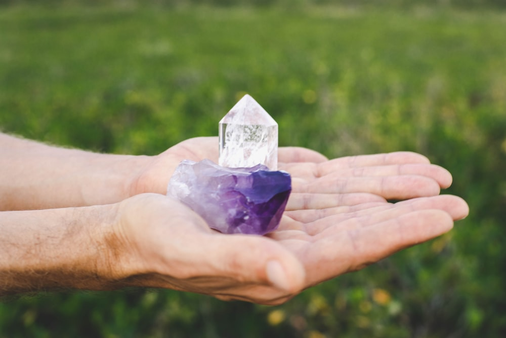 person holding purple and white glass pyramid