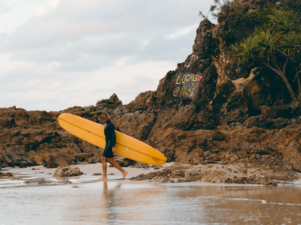 person holding yellow surfboard walking on beach during daytime