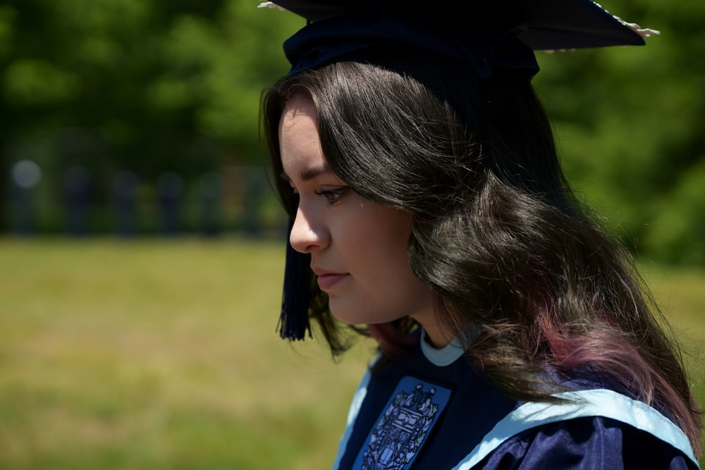 woman in blue academic dress and black academic hat