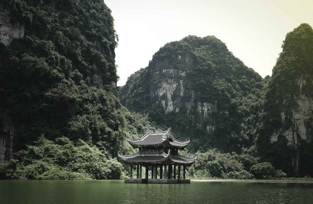 brown wooden house on lake near mountain during daytime