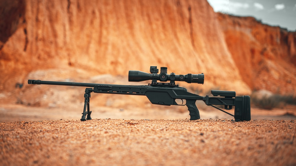 black rifle on brown sand