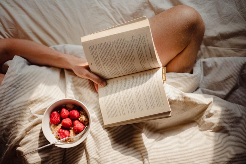 person reading book on white textile