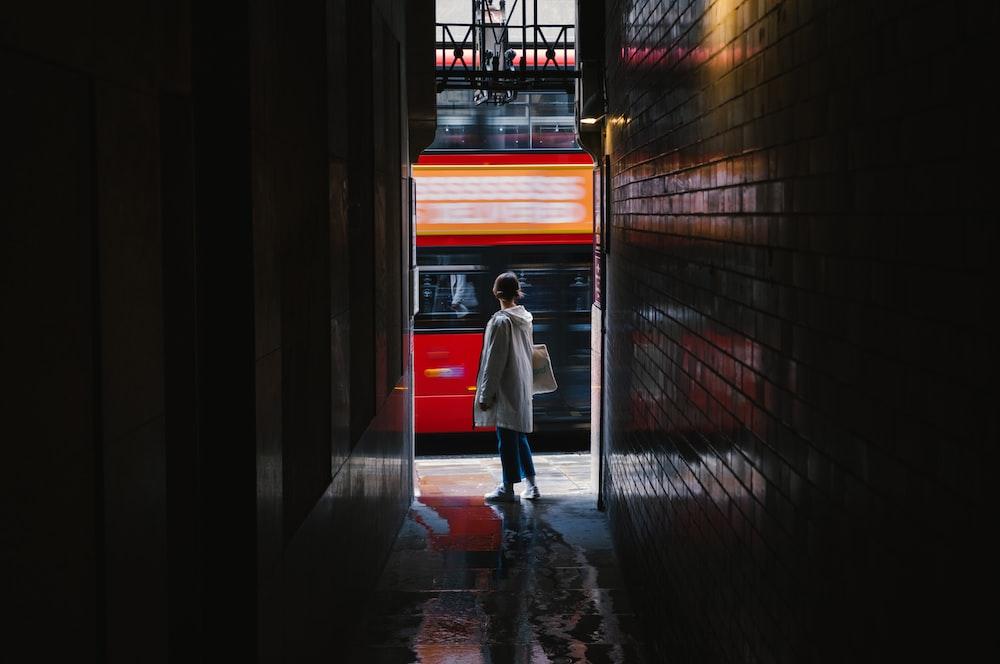 woman in white coat walking on hallway