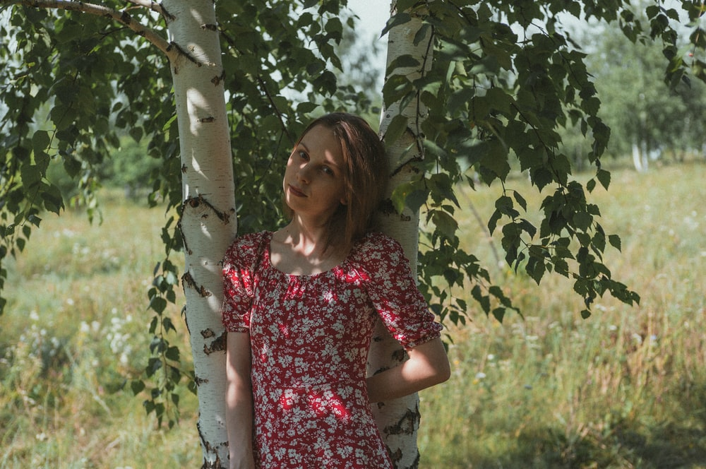woman in red and white floral dress standing beside green leaf tree during daytime