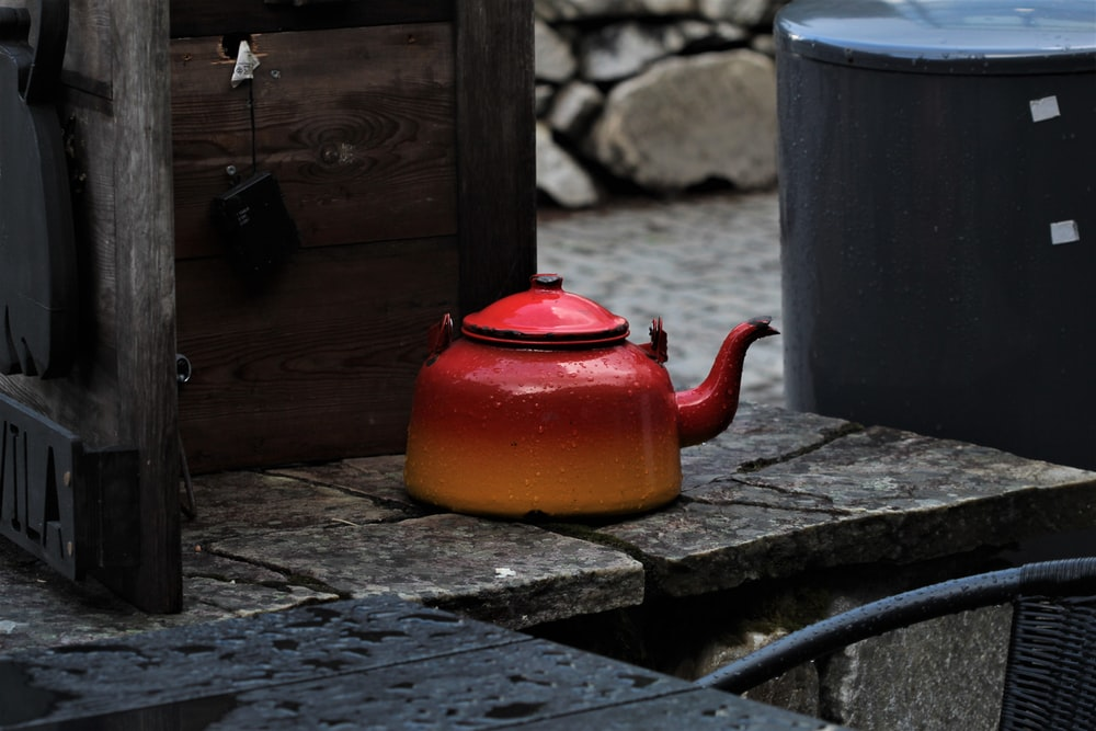 orange kettle on brown wooden table