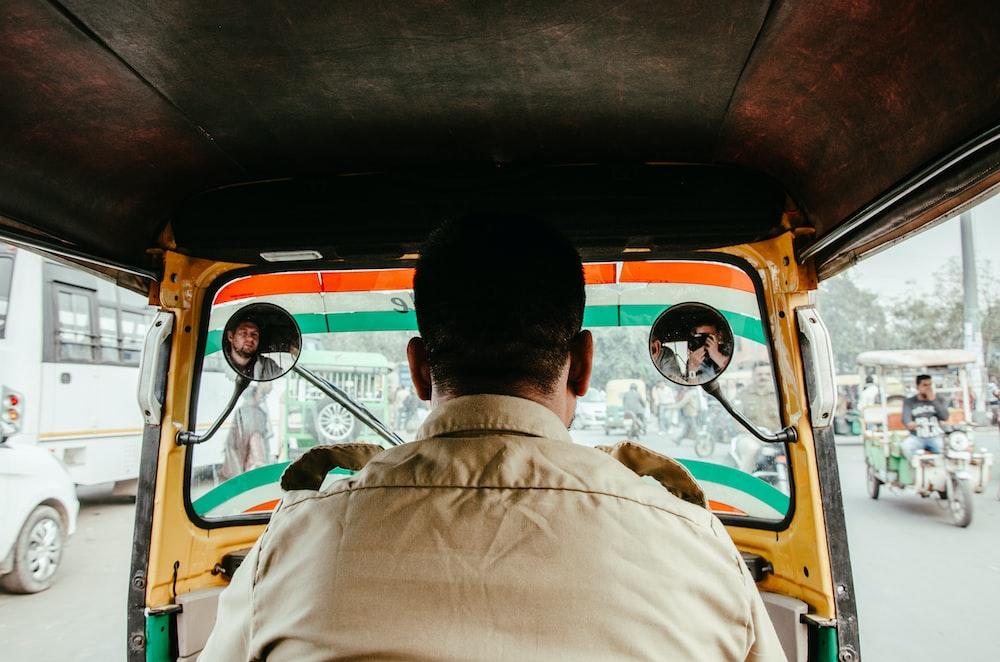 man in white button up shirt sitting inside orange bus during daytime