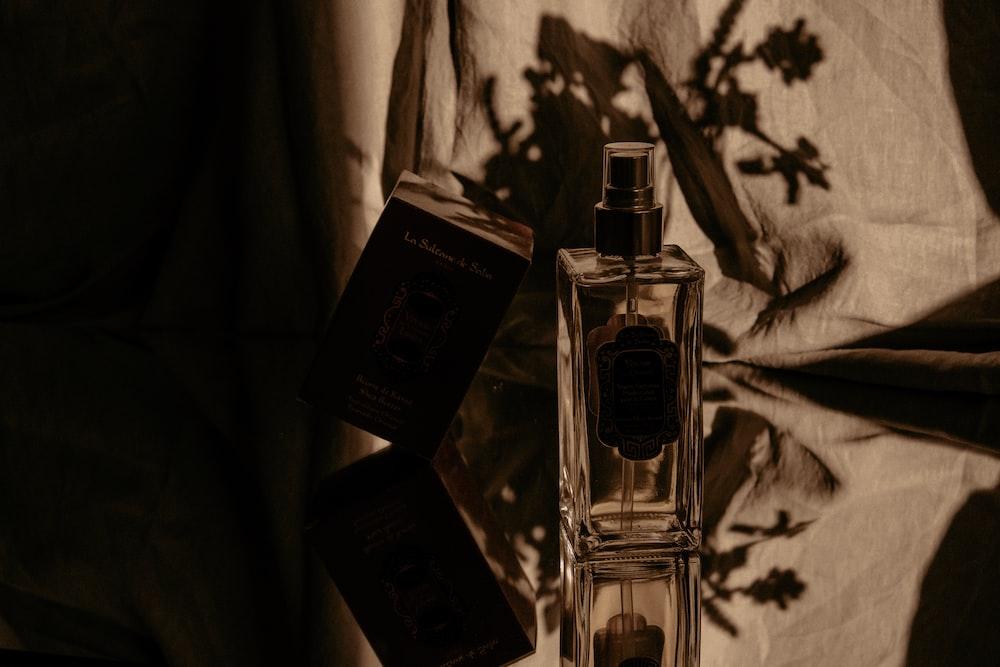 clear glass perfume bottle on black box