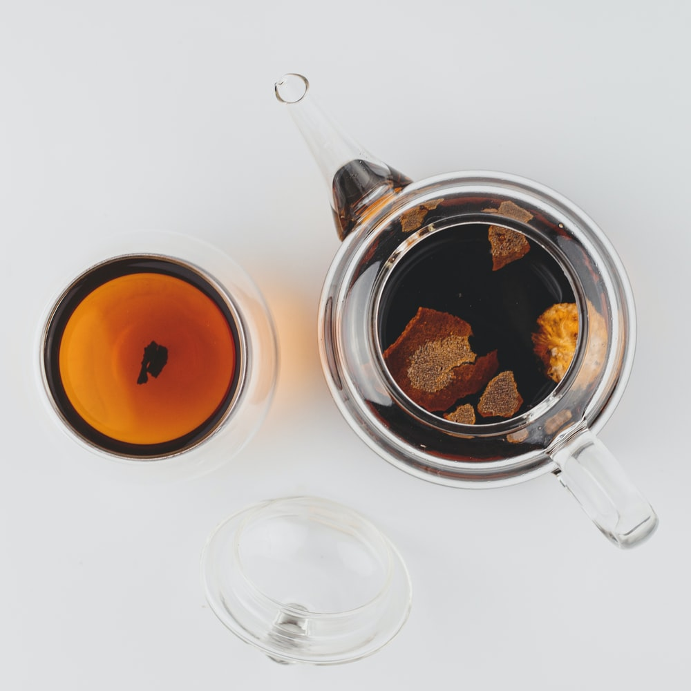 clear glass cup with brown liquid