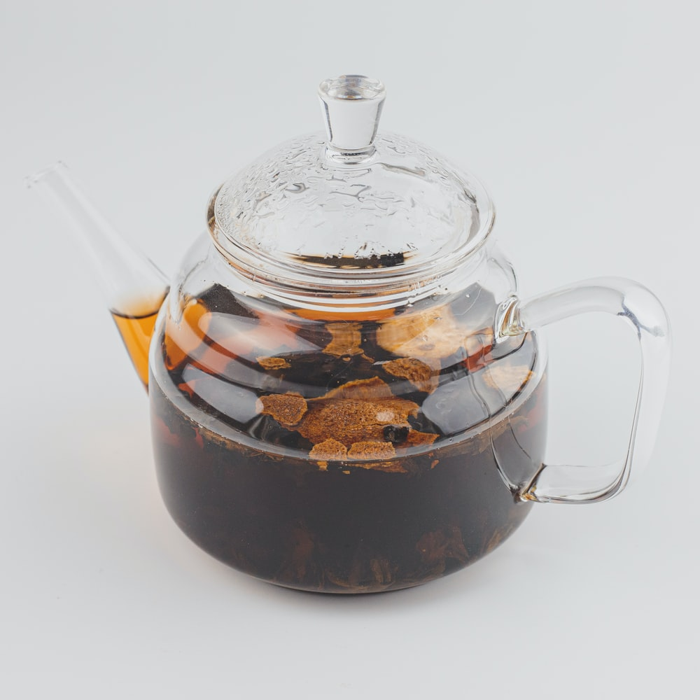 clear glass teapot with brown liquid