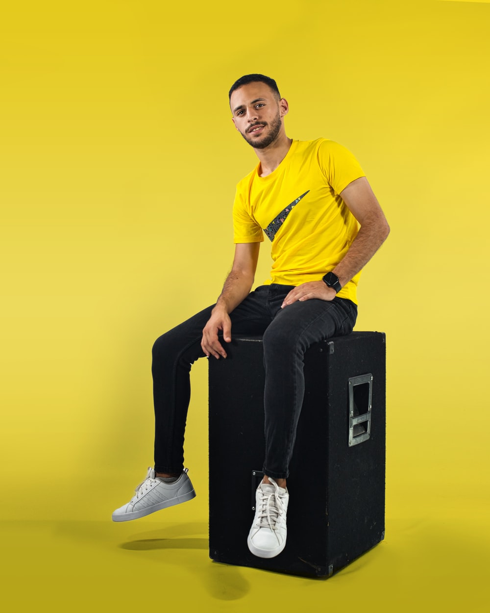 man in yellow crew neck t-shirt and black pants sitting on black box
