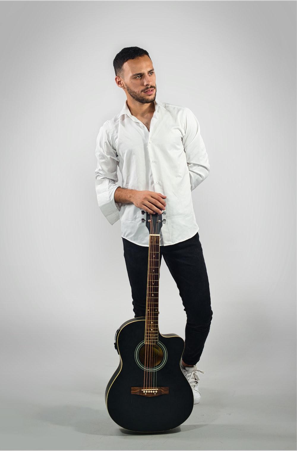 man in white dress shirt holding black acoustic guitar