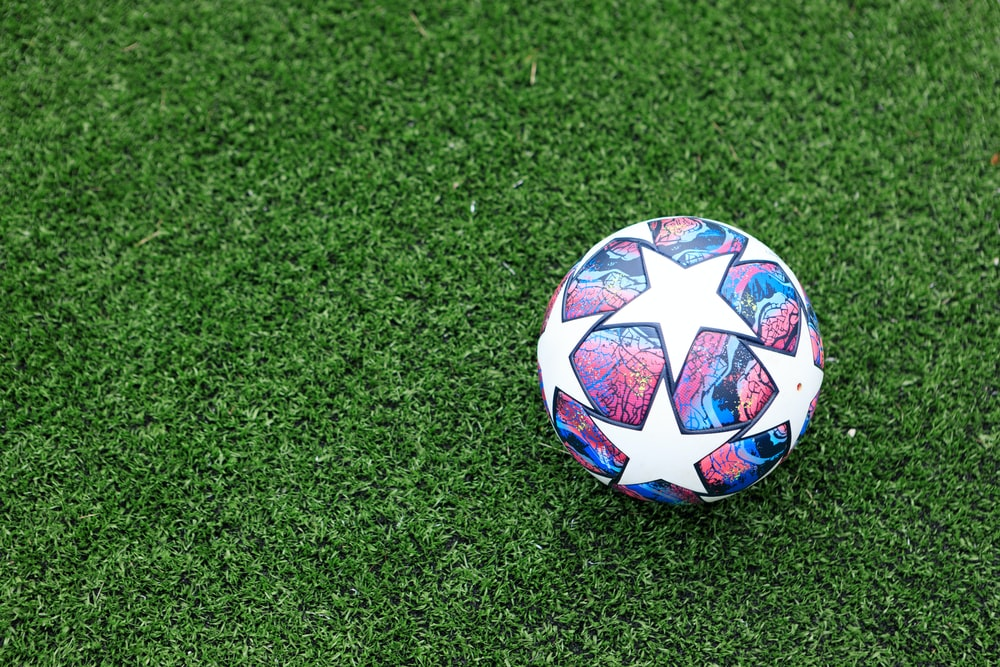 white blue and red soccer ball on green grass