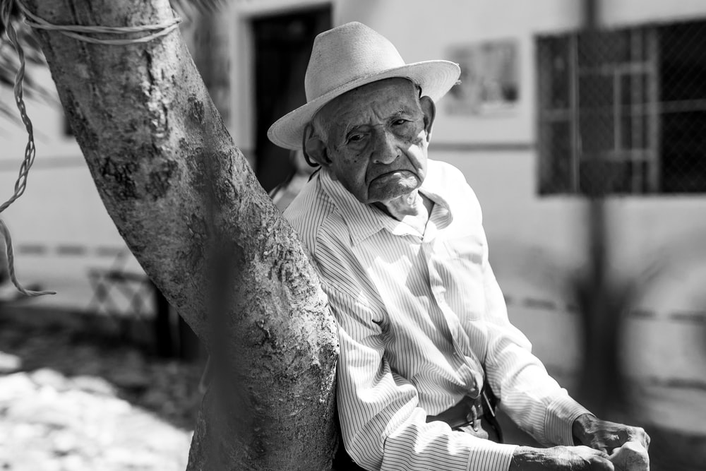 man in white dress shirt and hat sitting on chair