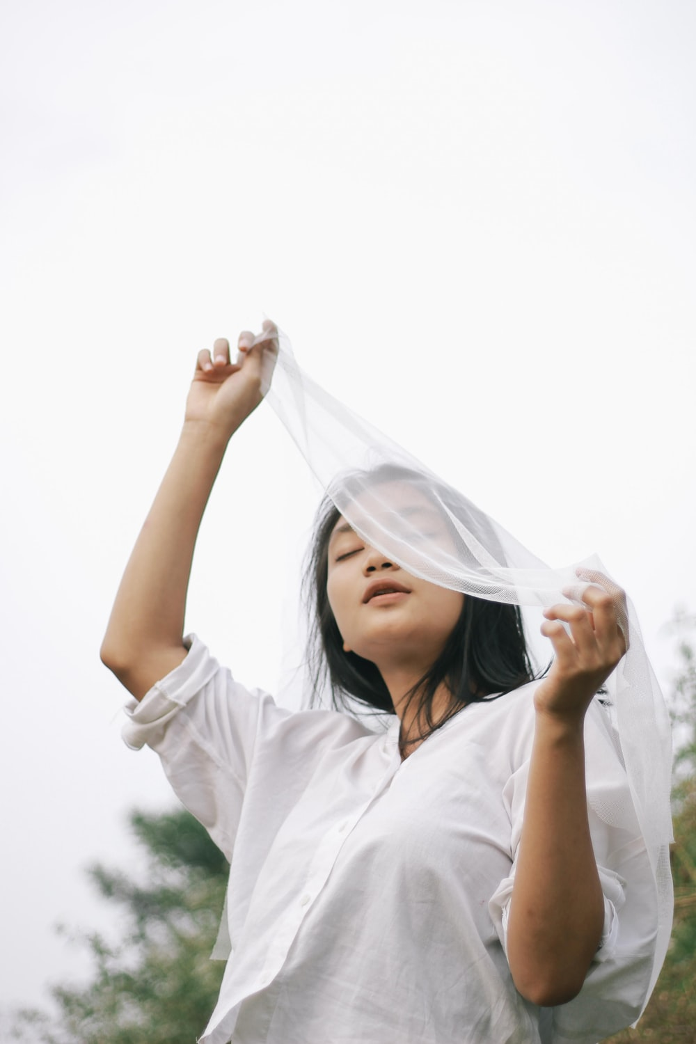 woman in white hijab covering her face with white sheer textile