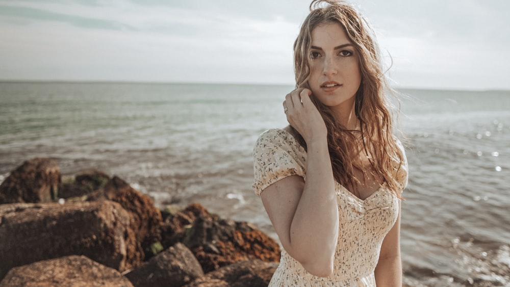 woman in white lace dress sitting on rock near sea during daytime