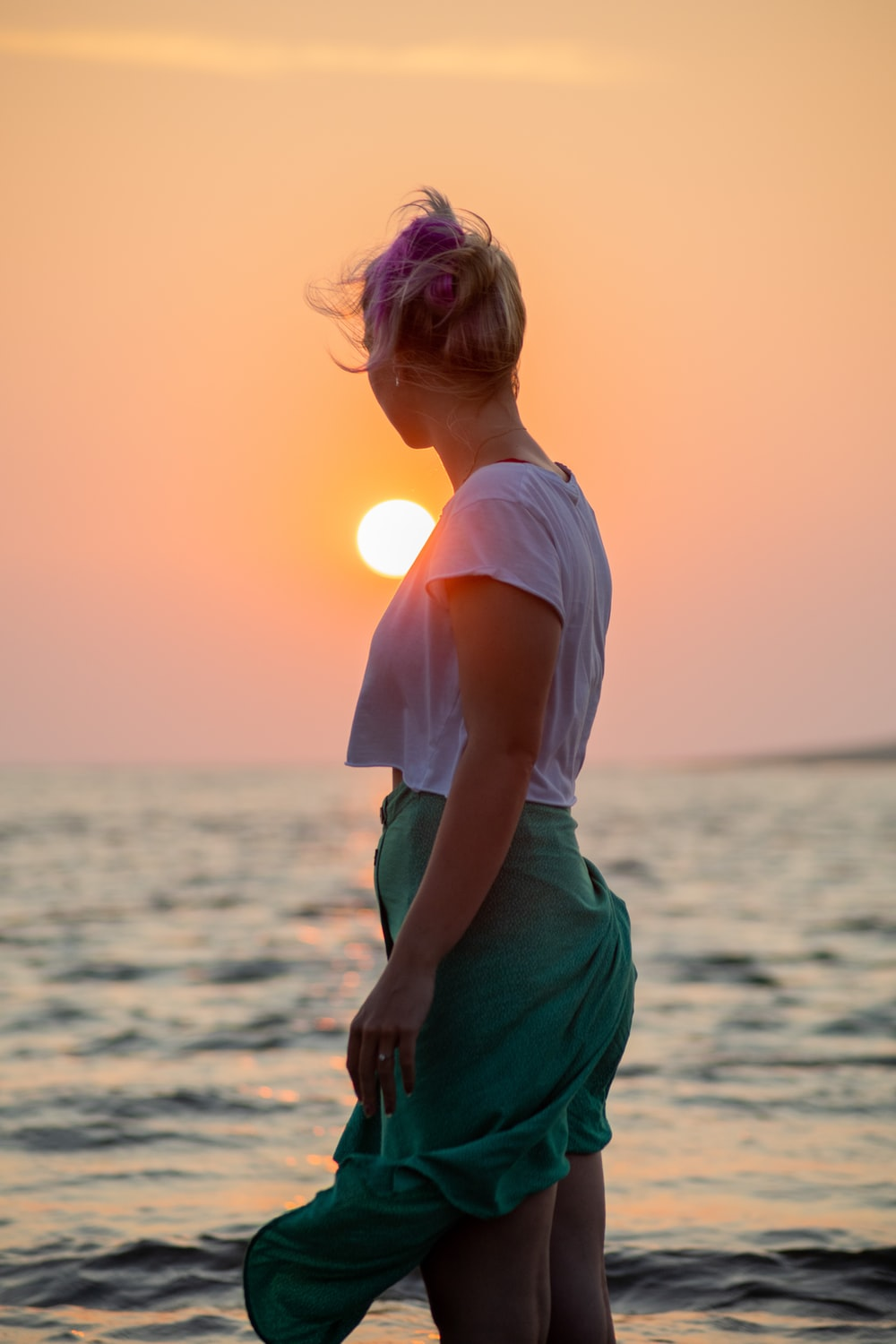 woman in white shirt and green skirt standing on beach during sunset