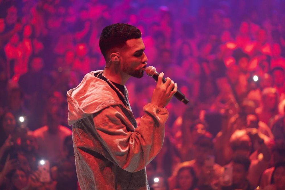 man in brown coat singing