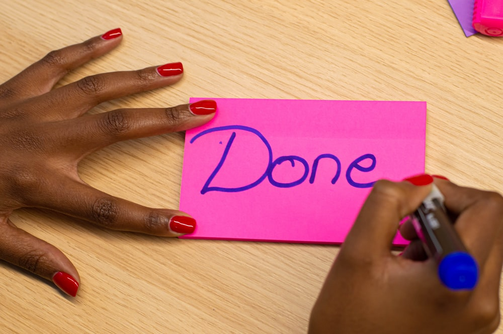 person with red manicure holding purple paper