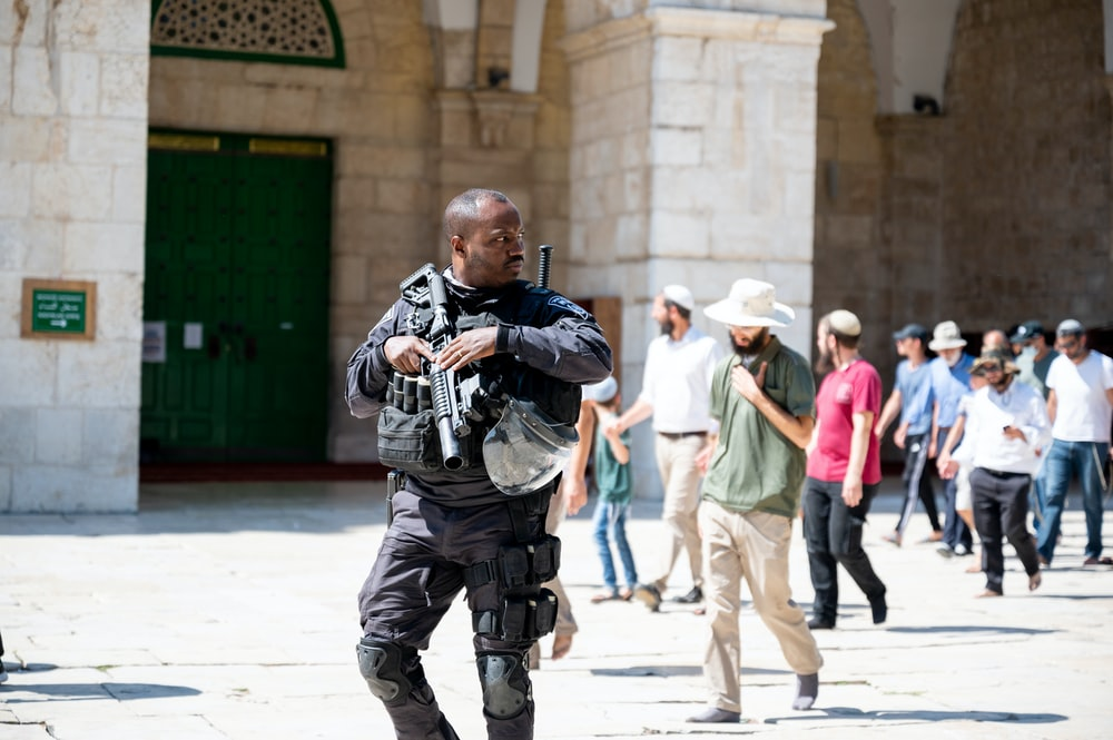 man in blue denim jeans carrying black dslr camera