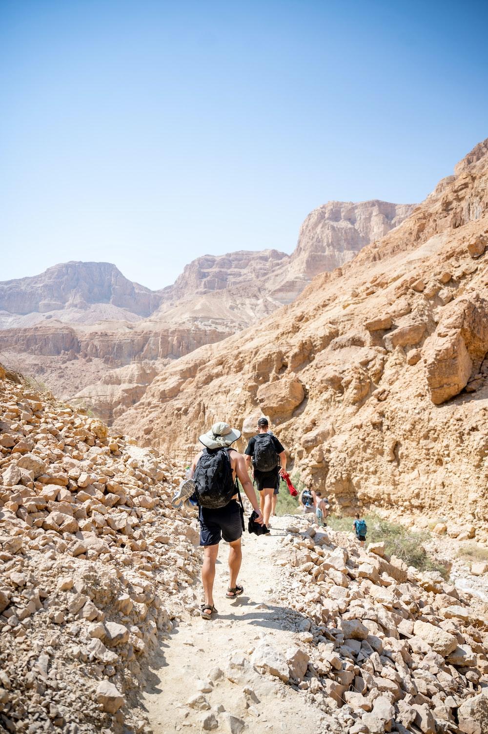 man in black t-shirt and black shorts walking on rocky mountain during daytime