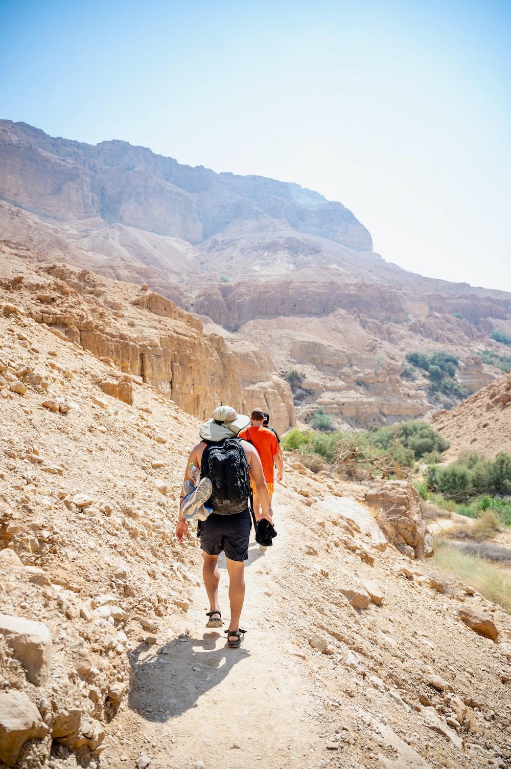 man in white shirt and black shorts walking on brown rocky mountain during daytime