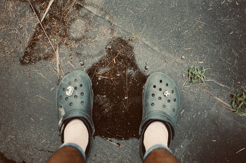 person wearing gray rubber clogs