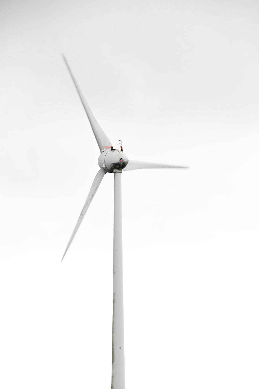 white wind turbine under white sky