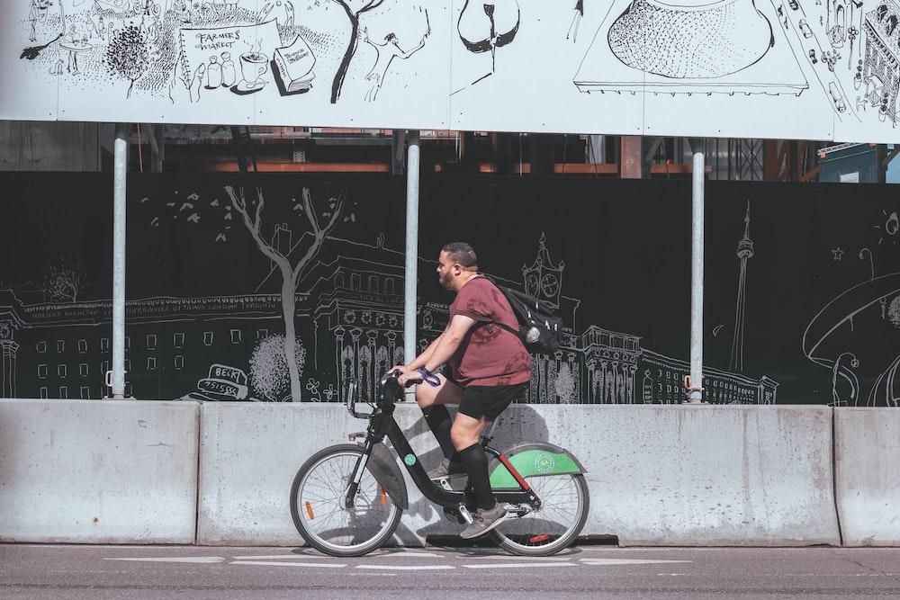 man in brown shirt riding on black bmx bike