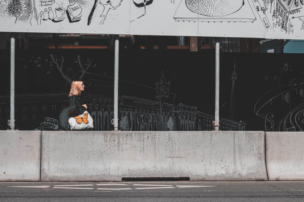 woman in white jacket sitting on gray concrete bench