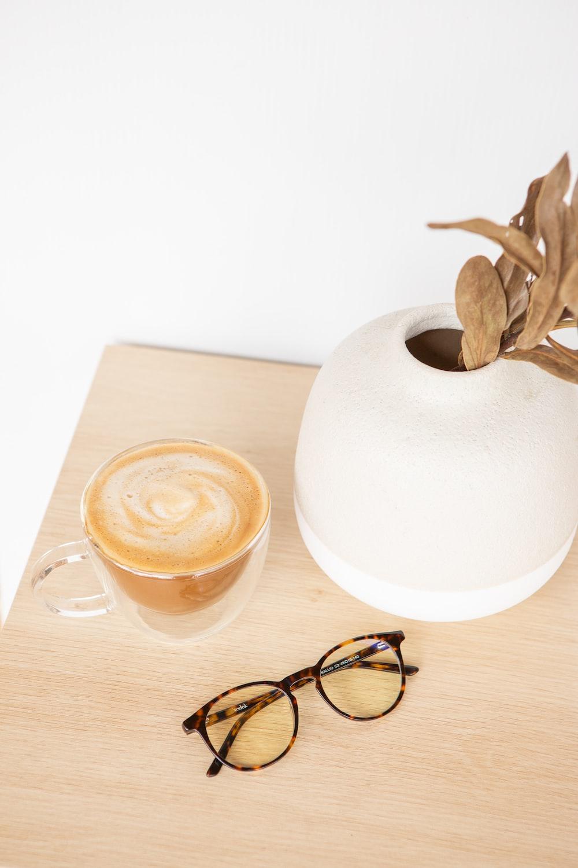 white round ceramic plate beside black framed eyeglasses