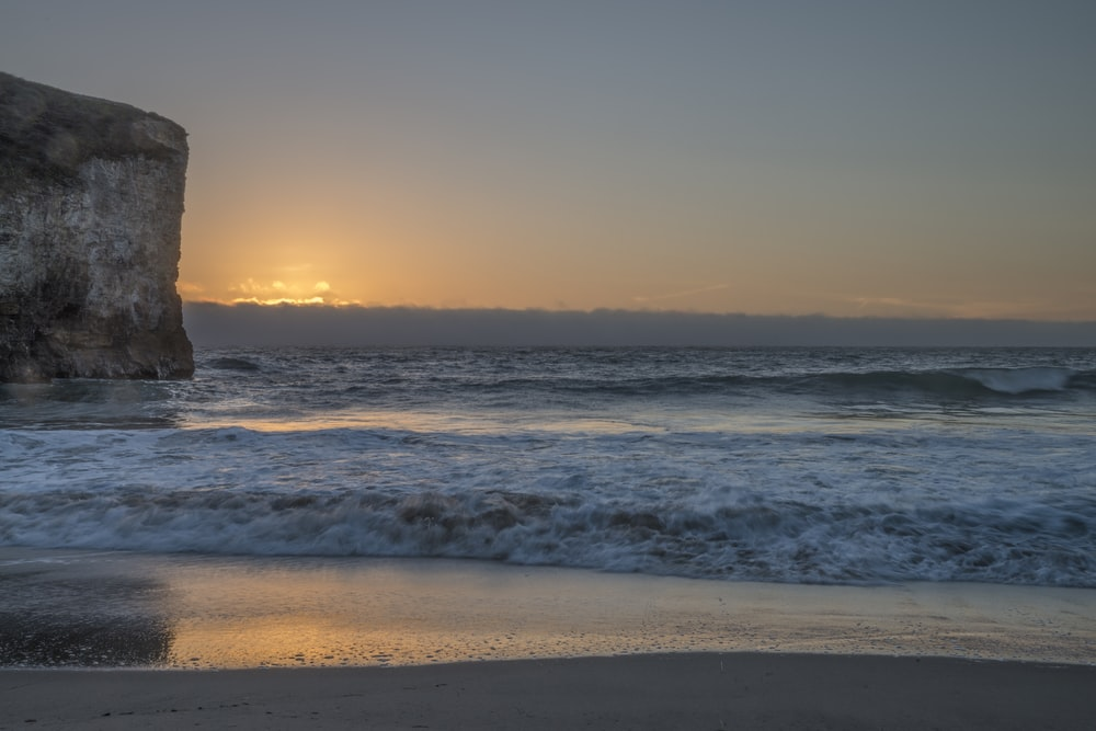 person standing on beach shore during sunset