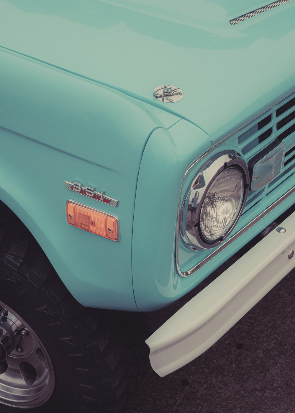 teal car with chrome wheel