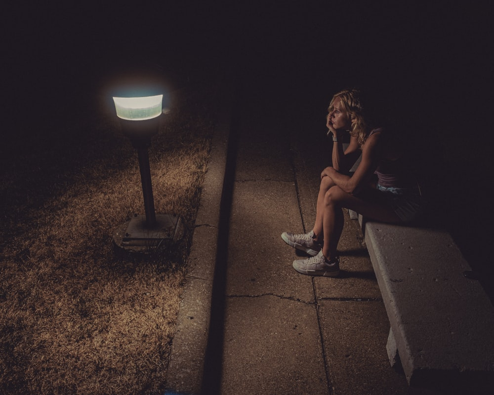 woman in black tank top sitting on concrete floor