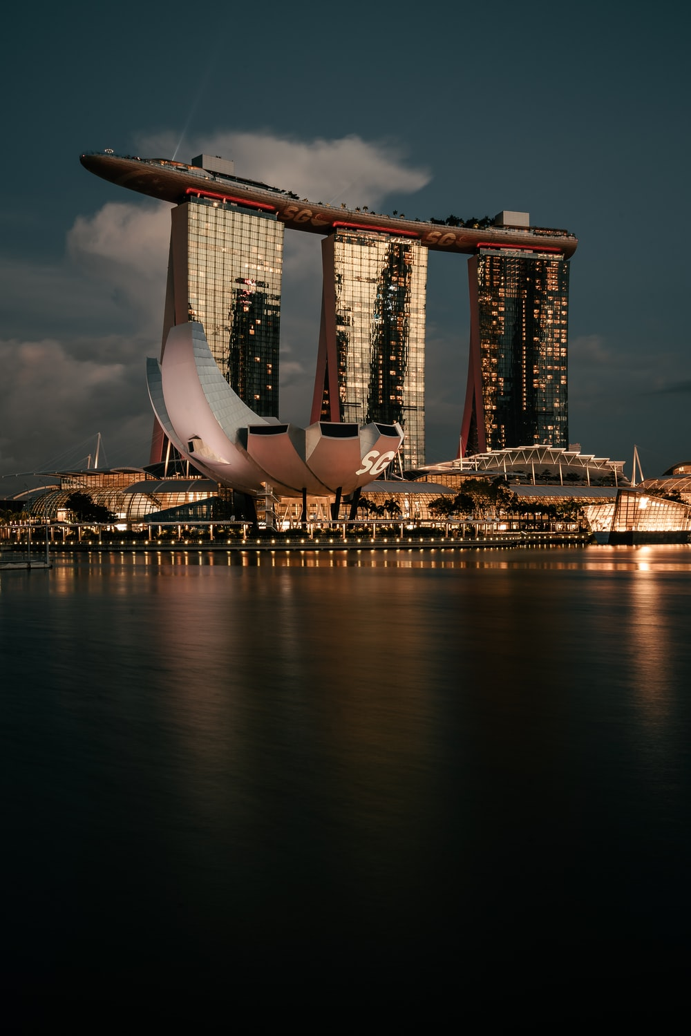 white and brown building near body of water during night time