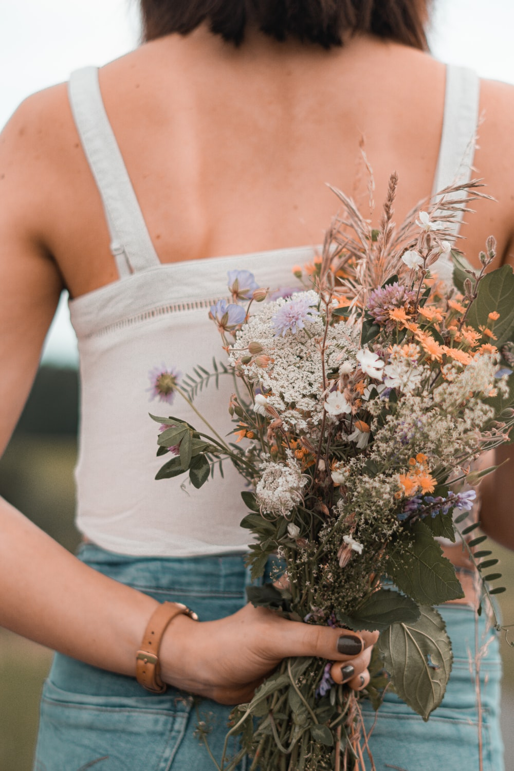 woman in white tank top holding bouquet of flowers