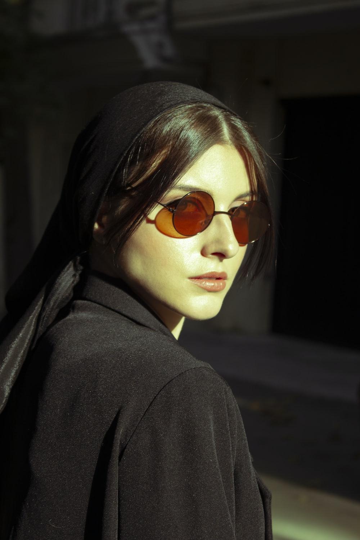 woman in black coat wearing brown sunglasses