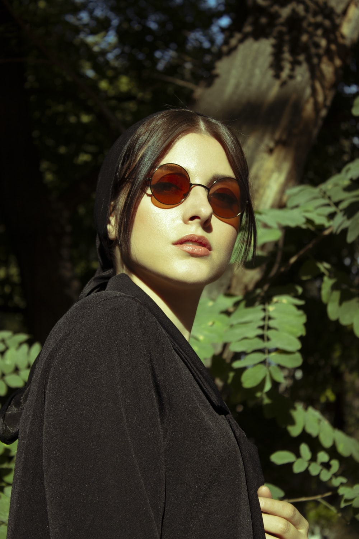 woman in black coat and brown sunglasses
